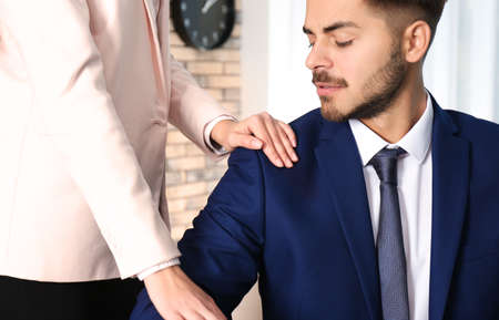 Woman molesting her male colleague in office, closeup. Sexual harassment at work Stock Photo