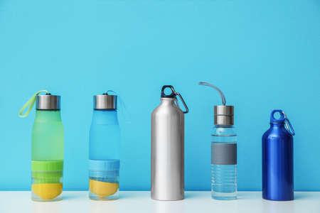 Different water bottles for sports on color background