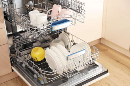 Open dishwasher with clean tableware in kitchen Imagens