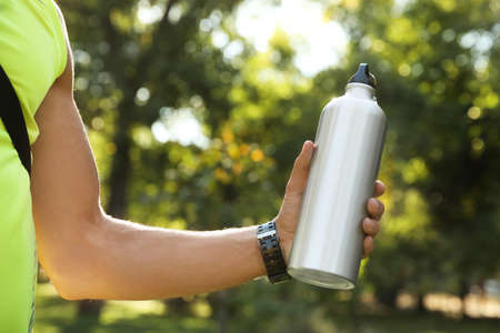 Young man holding bottle of water in park on sunny day, closeup 版權商用圖片