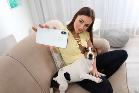 Beautiful woman taking selfie with her dog on sofa at home