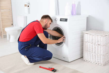 Young plumber examining washing machine in bathroom