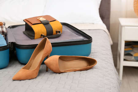 Suitcase packed for trip on bed in room