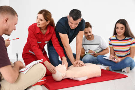 Group of people with instructor practicing CPR on mannequin at first aid class indoors Stock Photo