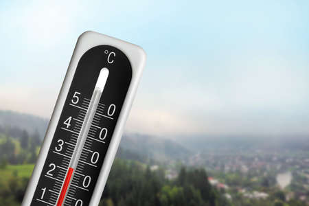 High temperature on thermometer and view of mountain village Фото со стока