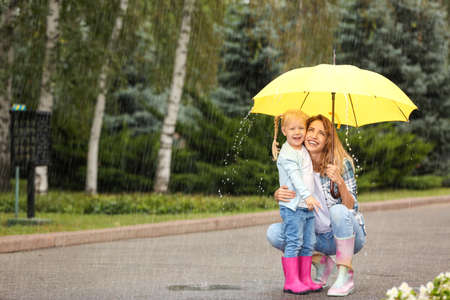 Happy mother and daughter with yellow umbrella in park on rainy day. Space for text