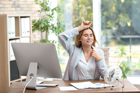 Businesswoman refreshing from heat in front of fan at workplace Imagens
