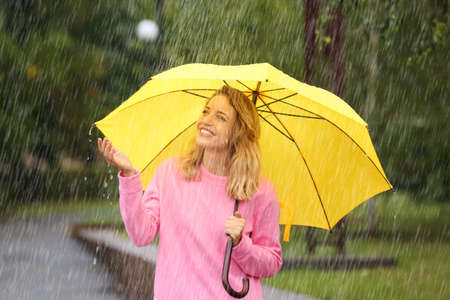 Portrait of young woman with yellow umbrella in park on rainy day