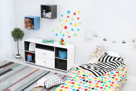 Modern child room interior with comfortable bed and striped carpet