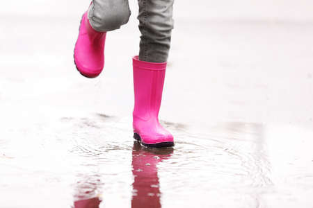 Little girl wearing rubber boots splashing in puddle on rainy day, focus of legs. Autumn walk
