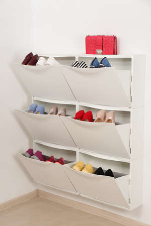 Shoe cabinet with footwear in room. Storage ideas Stok Fotoğraf