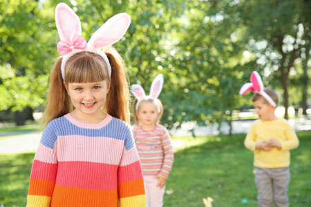 Cute little girl with bunny ears in park. Easter celebration Stock Photo - 112737034