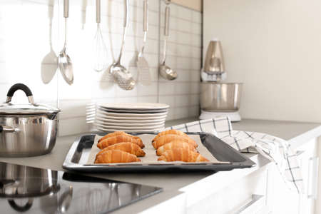 Oven sheet with freshly baked croissants on kitchen counter Zdjęcie Seryjne