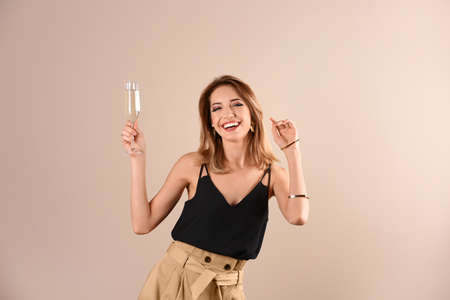 Portrait of happy woman with champagne in glass on color background