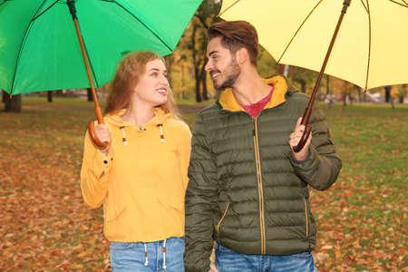 Happy couple with umbrellas walking in park