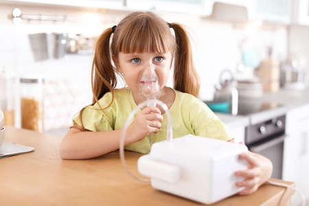 Little girl using asthma machine at table in kitchen