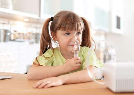 Niña con máquina para el asma en la mesa de la cocina