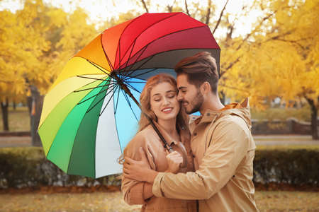 Happy couple with colorful umbrella in park