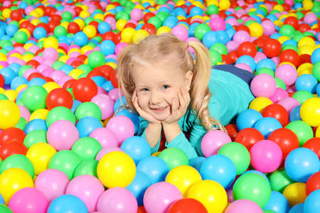 Cute child playing in ball pit indoors Stock Photo