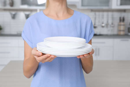 Woman with stack of clean dishes in kitchen, closeup Фото со стока - 112642682