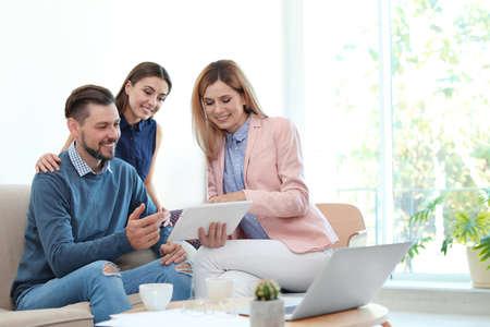 Weiblicher Immobilienmakler, der mit Paar im Büro arbeitet working