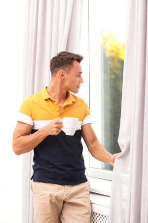 Young man opening window curtains at home