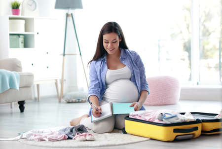 Pregnant woman writing packing list for maternity hospital at home Zdjęcie Seryjne