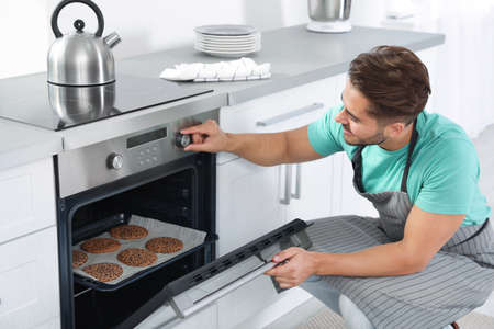 Young man baking cookies in oven at home