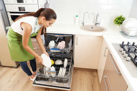 Beautiful young woman loading dishwasher in kitchen. Cleaning chores 免版税图像