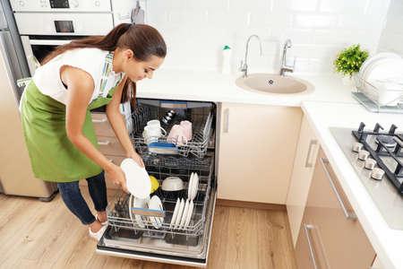 Lavastoviglie di caricamento della bella giovane donna in cucina. Lavoretti di pulizia Archivio Fotografico