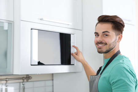 Young man using modern microwave oven at home