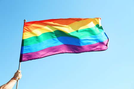 Gay man holding rainbow LGBT flag on blue sky background Stock Photo