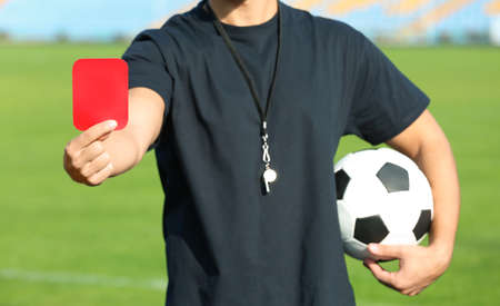 Football referee showing red card at stadium, closeup Stock Photo