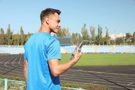 Young sporty man holding bottle of water at stadium on sunny day. Space for text