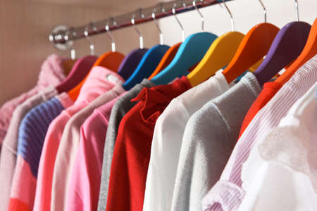 Stylish girl's clothes hanging in wardrobe, closeup Stock Photo