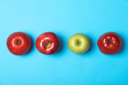 Rangée de pommes rouges avec une verte sur fond de couleur, vue de dessus. Sois différent