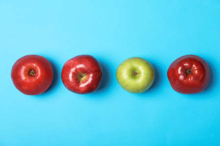 Row of red apples with green one on color background, top view. Be different