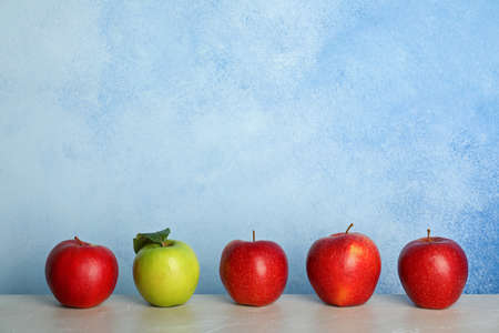 Row of red apples with green one on table. Be different