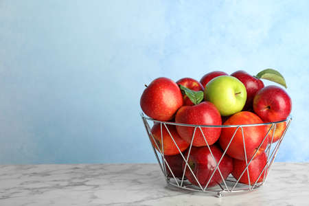 Different apple among red ones in metal basket on table. Space for text Foto de archivo