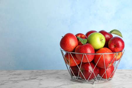Pomme différente parmi les rouges dans un panier en métal sur la table. Espace pour le texte Banque d'images