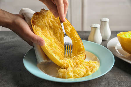 Woman scraping flesh of cooked spaghetti squash with fork on table, closeup
