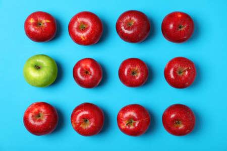Manzana verde entre las rojas sobre fondo de color, vista superior. Sé diferente Foto de archivo