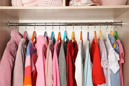 Wardrobe with stylish girl's clothes hanging on rack Stock Photo