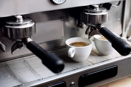 Coffee machine with cups on drip tray, closeup Imagens