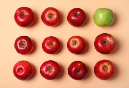 Pomme verte parmi les rouges sur fond de couleur, vue de dessus. Sois différent