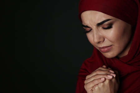 Portrait of sad Muslim woman in hijab  praying on dark background. Space for text Reklamní fotografie