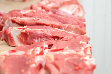 Pieces of fresh raw meat on counter in butcher shop Imagens