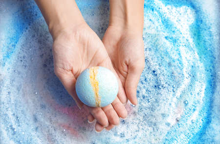 Woman holding color bath bomb over foam, top view