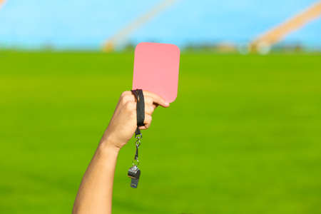 Football referee holding red card and whistle at stadium, closeup