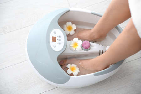 Woman with beautiful legs using foot bath at home, closeup. Spa treatment